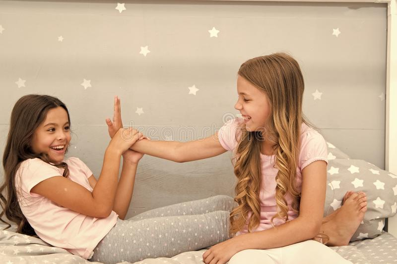 Sisters leisure. Girls in cute pajamas spend time together in bedroom. Sisters communicate while relax in bedroom royalty free stock image