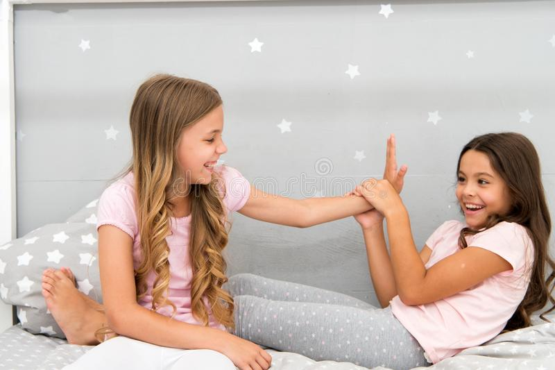 Sisters leisure. Girls in cute pajamas spend time together in bedroom. Sisters communicate while relax in bedroom royalty free stock photos