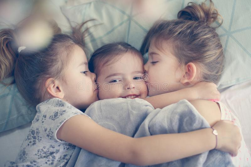 Sisters love. Kids in bed. Three little girls lying in bed and playing. Space for copy stock photography