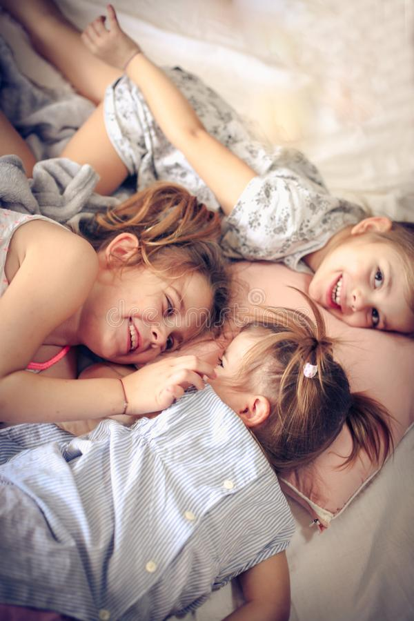 Sisters love. Three little girls lying on bed. Space for copy stock image