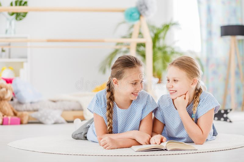 Sisters lying on the floor royalty free stock photos