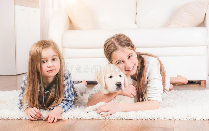 Sisters lying together with cute retriever puppy royalty free stock images