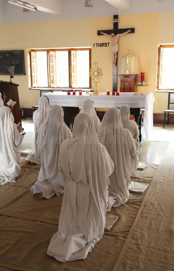 Sisters of Mother Teresa`s Missionaries of Charity in prayer in the chapel of the Mother House, Kolkata. India at February 08, 2014 royalty free stock photo