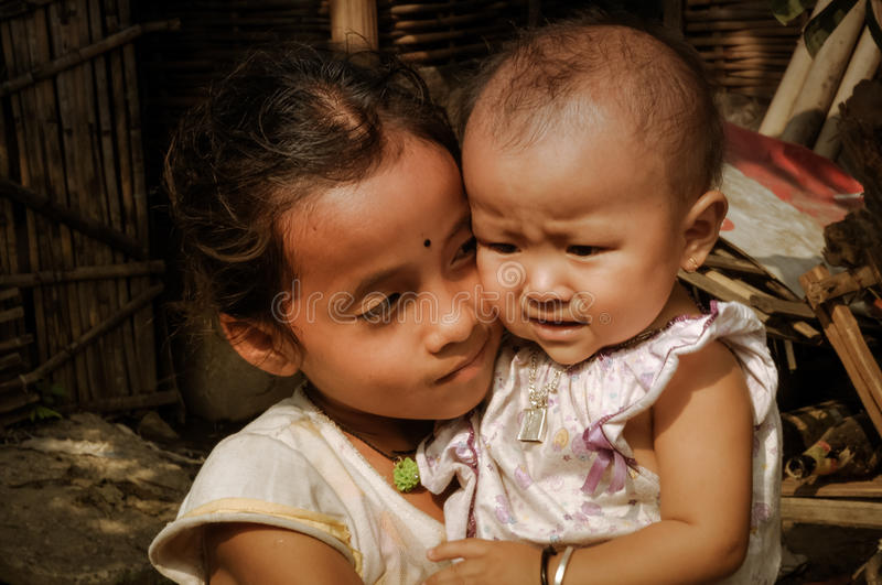 Sisters in Nepal. Damak, Nepal - circa May 2012: Young girl with dot on her forehead holds her younger sister in pink dress and looks at her at Nepali refugee stock photo