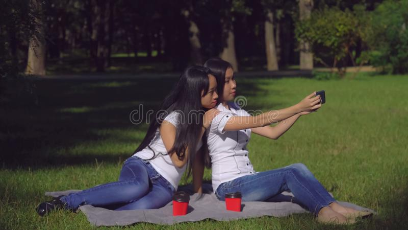 Sisters in park posed for photo. Two asian girls pretend happiness for selfie photo. Women using smartphone outdoors. Unhappy friends sitting on lawn with fresh stock photography