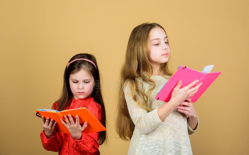 Sisters pick books to read together. Adorable girls love books. Opening doors through literacy. Kids girls with books or. Notepads. Education and kids royalty free stock photo