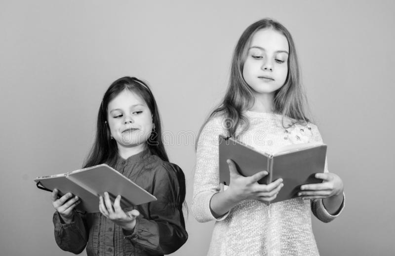 Sisters pick books to read together. Adorable girls love books. Secret diary. Opening doors through literacy. Kids girls. With books or notepads. Education and stock images