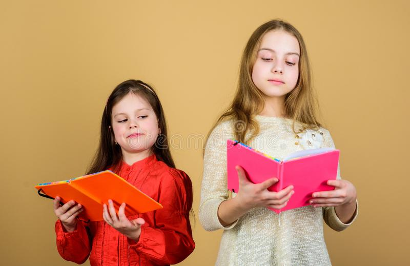 Sisters pick books to read together. Adorable girls love books. Secret diary. Opening doors through literacy. Kids girls. With books or notepads. Education and royalty free stock image
