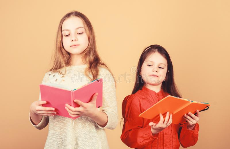 Sisters pick books to read together. Adorable girls love books. Secret diary. Opening doors through literacy. Kids girls. With books or notepads. Education and stock photos