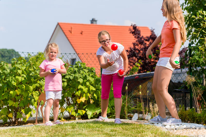 Sisters playing bocce in garden front or their home. Three sisters playing bocce in garden front or their home in summer stock image