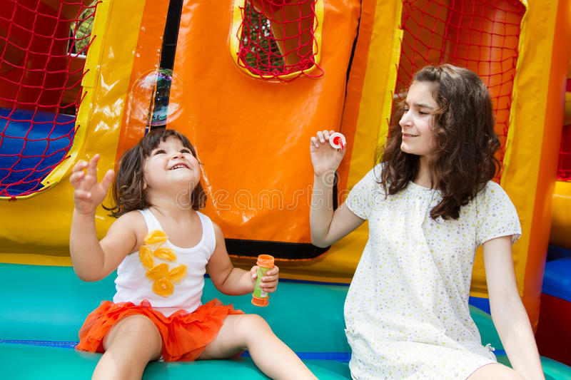 Sisters playing with bubble wand. Two cute young sisters playing with bubble wand at the bouncing castle on the background royalty free stock image