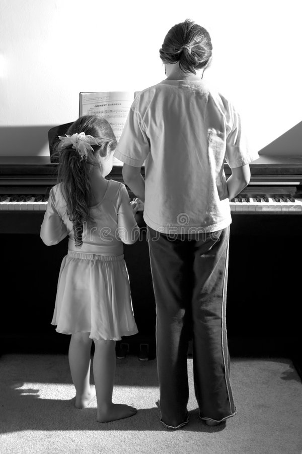 Sisters playing piano royalty free stock photography
