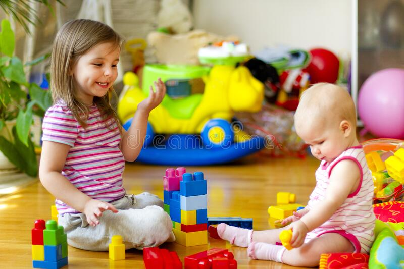 Sisters playing with toys at home. Little girl smiling and playing with baby sister while sitting on floor amidst colorful toys in nursery royalty free stock photo
