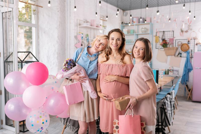 Two beautiful women standing near their pregnant sister with presents royalty free stock images