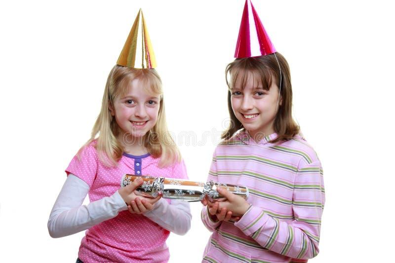 Sisters pulling a cracker at Christmas royalty free stock photos