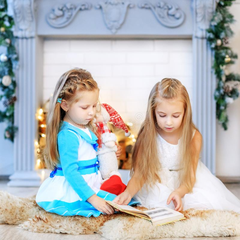 Sisters read a story at night. Concept New Year, Merry Christmas. Sisters read a story at night. How to instill a love of reading. Concept New Year, Merry royalty free stock images