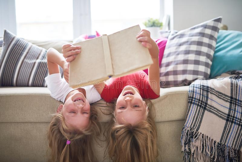 Sisters Reading Book Upside Down stock images