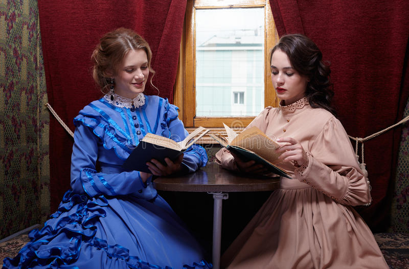Sisters in retro dress reading books in train compartment royalty free stock images
