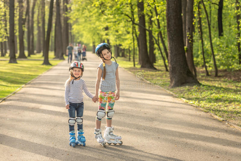 Sisters roller blading together, holding hands. Sisters roller blading together, both in helmets, holding hands in the park stock photos