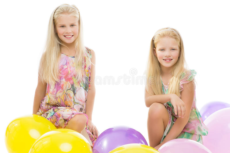 Sisters sitting in balloons stock photos