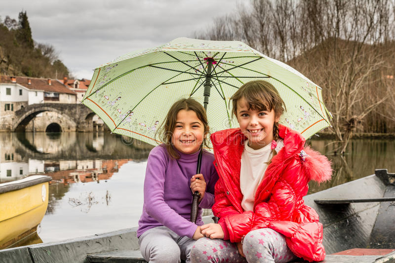Sisters sitting in the boat on the river and holding the umbrella stock photo