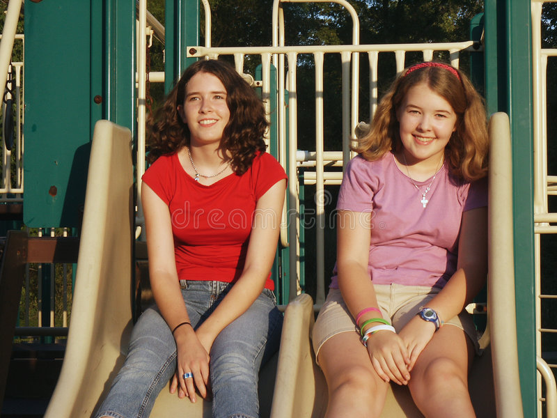 Sisters on slides stock image