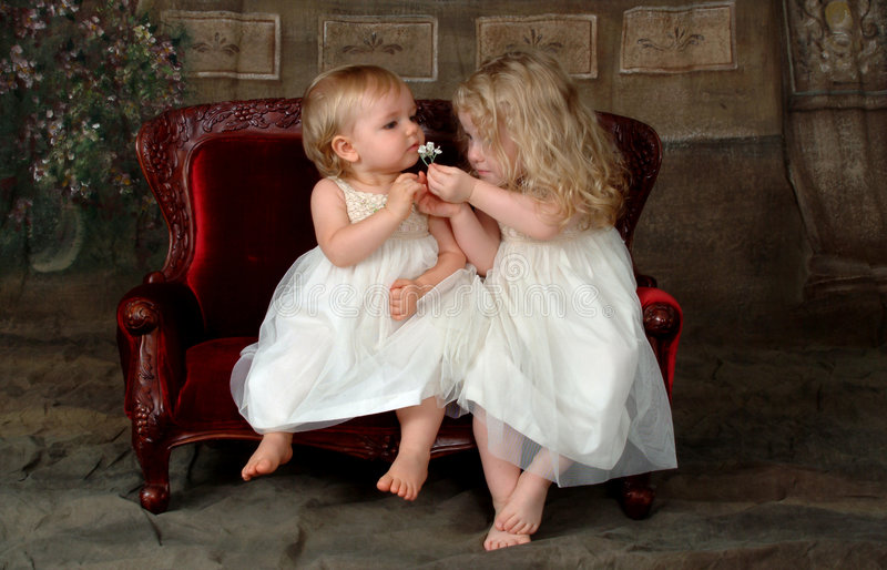 Sisters Smelling Flower. Sisters sitting together, smelling flower, on red velvet antique children's couch royalty free stock image