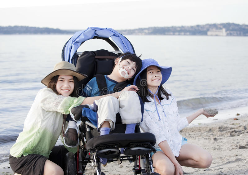 Sisters taking care of disabled brother on beach stock photo