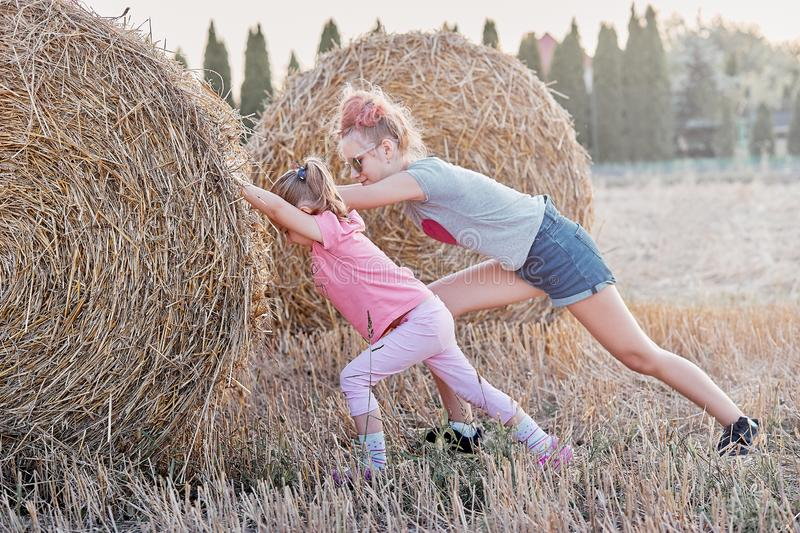 Sisters pushing hay bale playing together outdoors in the countryside stock photo