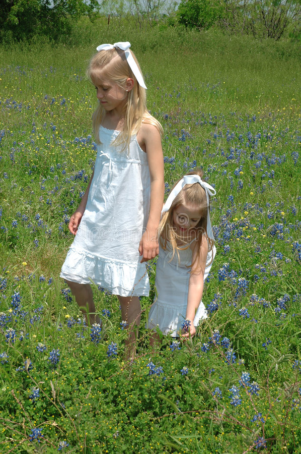 Sisters Together. Two sister spending the day in blue bonnet flowers Blue Bonnets are native Texas flowers. The Blue Bonnet is the State Flower of Texas, USA stock photography