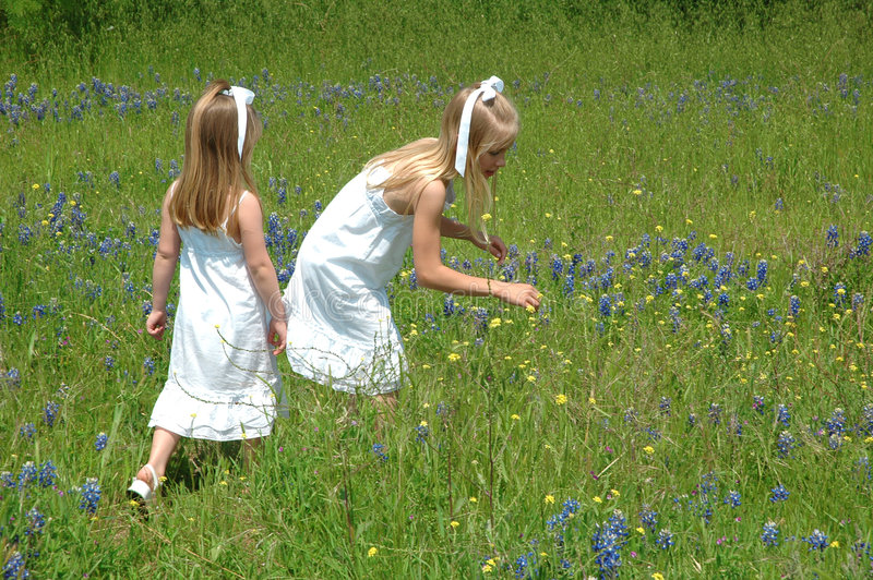 Sisters Together. Two sister spending the day in blue bonnet flowers Blue Bonnets are native Texas flowers. The Blue Bonnet is the State Flower of Texas, USA royalty free stock image