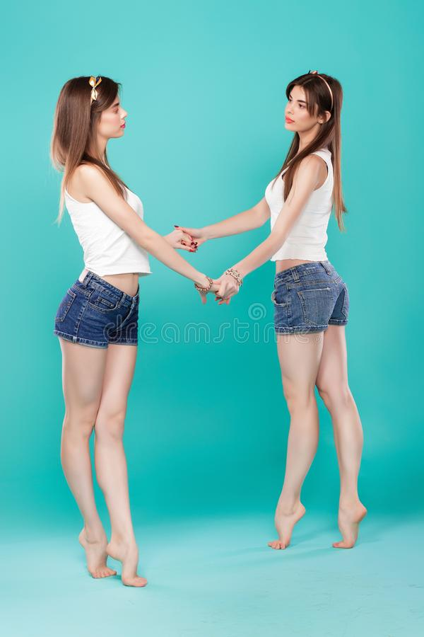Sisters twins on blue background. royalty free stock photography