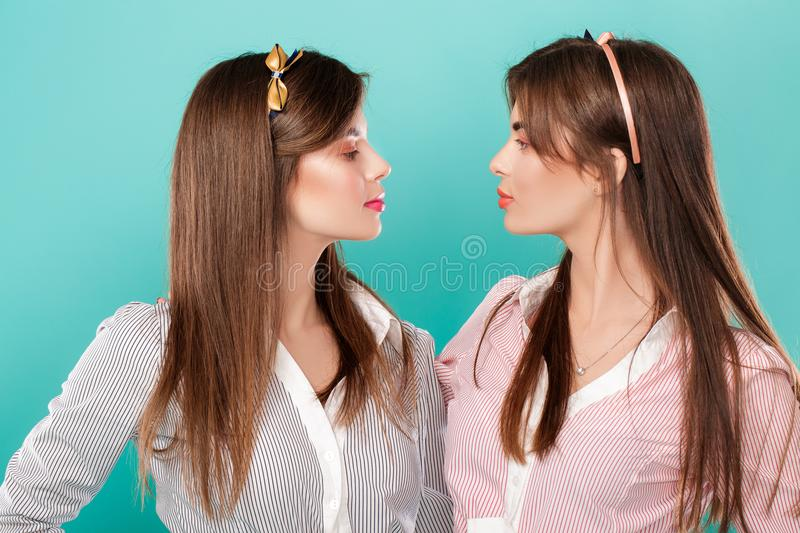 Sisters twins on blue background. stock image