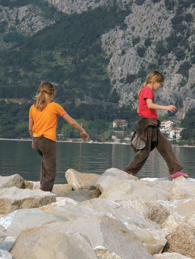 Sisters, twins playing on rock near sea stock photo