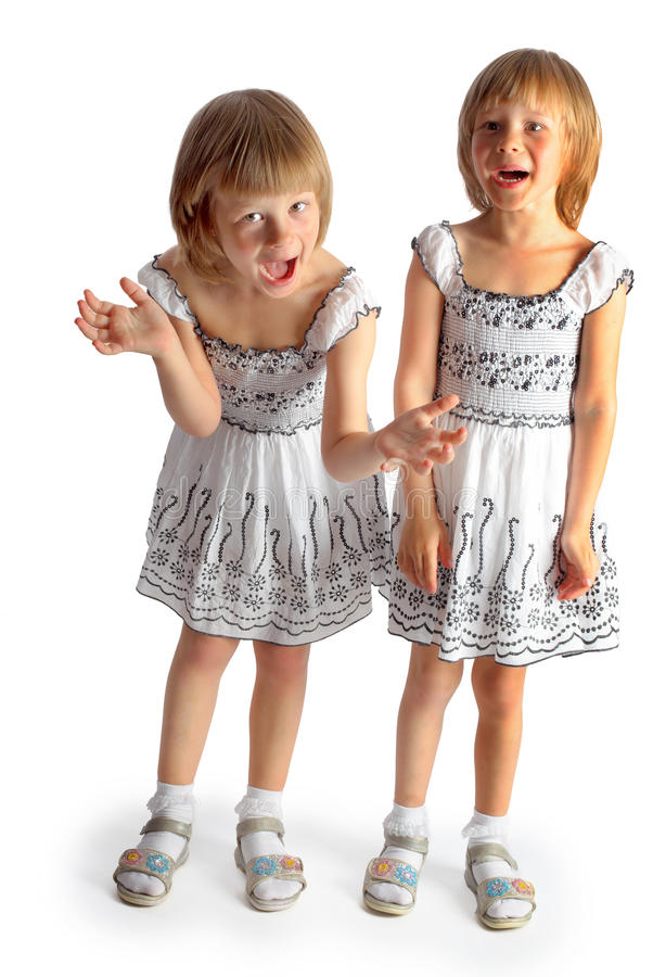Sisters twins in white dresses play. In studio on a white background stock photography