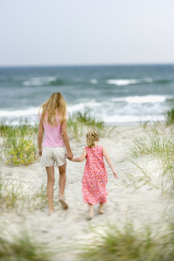 Sisters walking on beach. royalty free stock photography