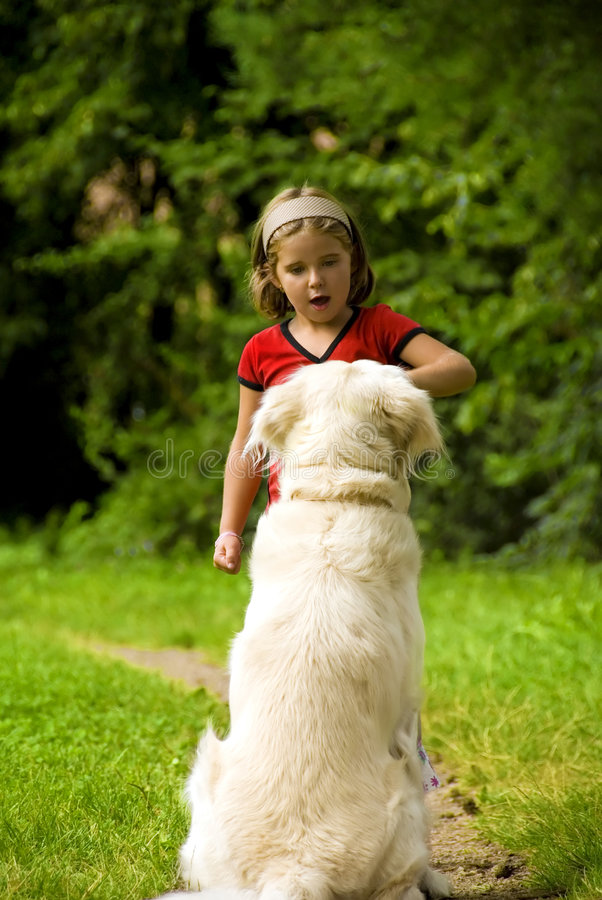 Sit down!. Small girl training her dog in meadow