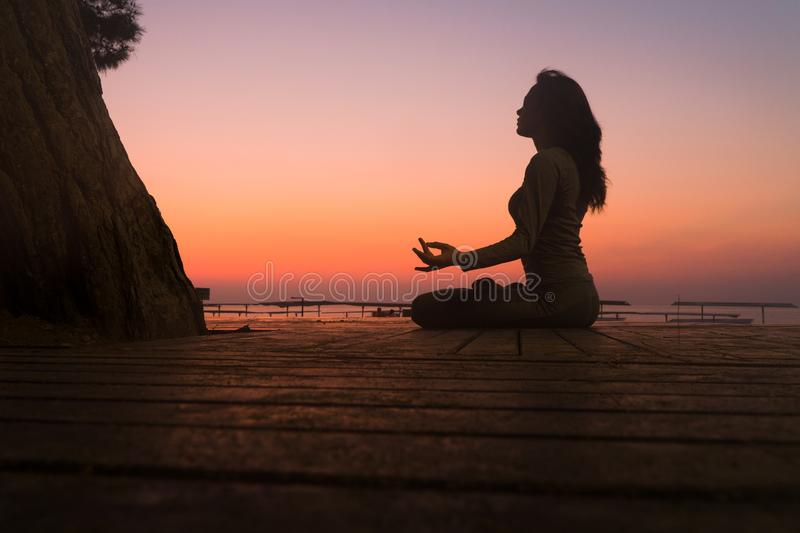 Do yoga at dawn. lotus position in the sun. Sit in lotus position at sunrise royalty free stock photos
