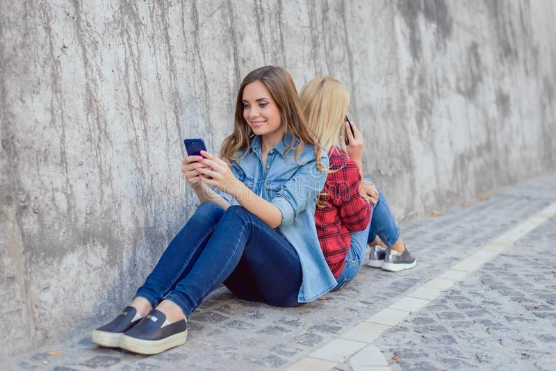 Sit texting cell call best age mobilephone watch play person people app store back-to-back concept. Cure beautiful pretty lovely royalty free stock photos