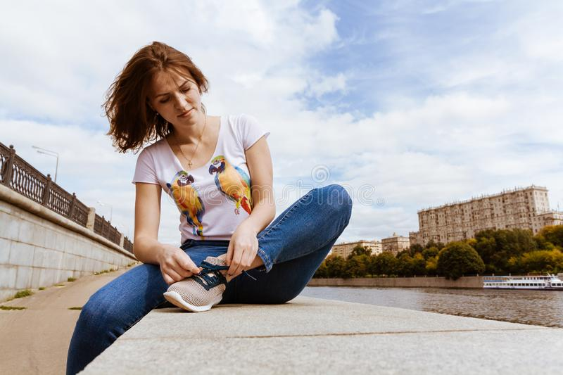 Sit and tie shoes with travel. portrait of pretty girl in blue jeans tying shoelaces on the old embankment stock images