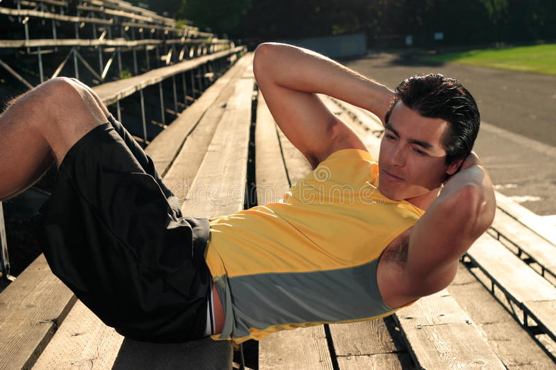 Sit Ups On Bleachers. A young athletic male doing sit ups on sports track bleachers stock photo