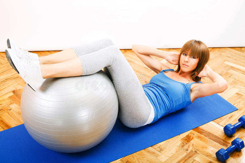 Sit-ups. Fitness girl doing Sit-ups with pilates ball royalty free stock photography