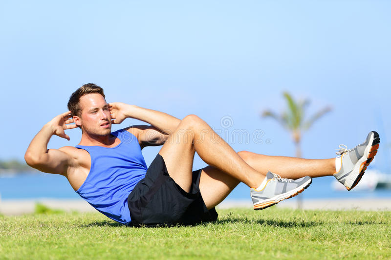 Sit ups - fitness man exercising sit up outside royalty free stock photos