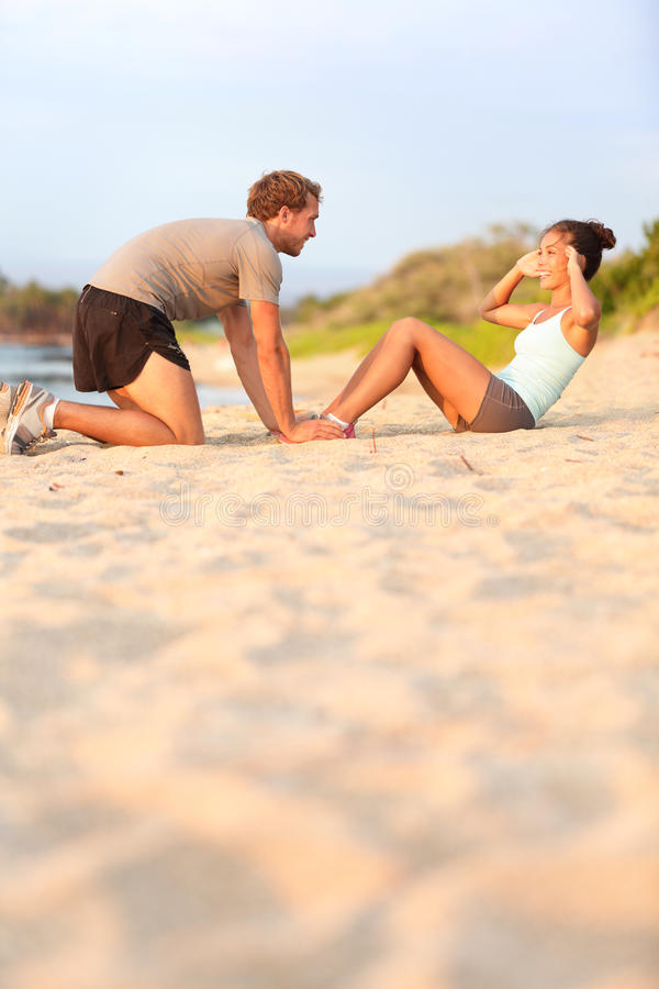 Sit ups fitness woman - male helping happy smiling stock photo