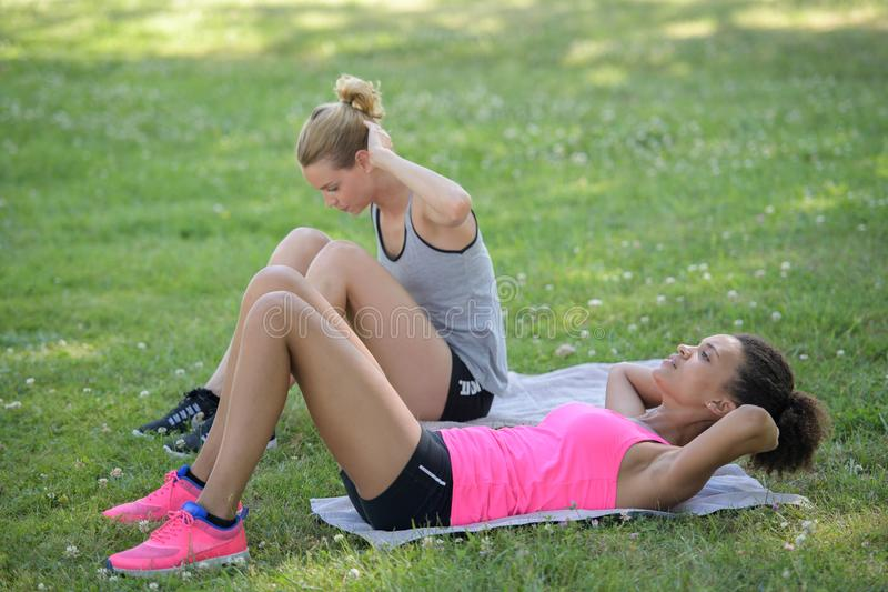 Sit-ups fitness women doing situps training core abs exercises outside royalty free stock photo