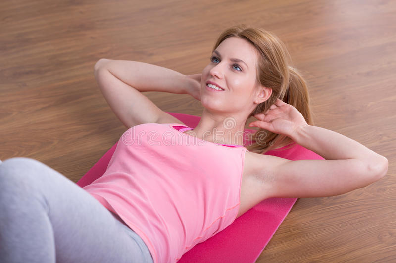 Sit-ups on the floor. Young woman is doing sit-ups on the floor royalty free stock photography