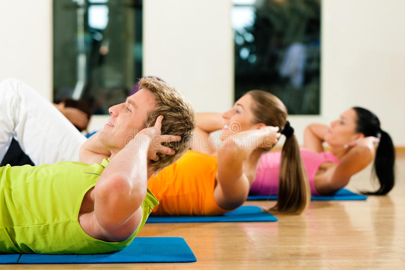 Sit-ups in gym for fitness. People, man and women, exercising doing sit-ups in gym or fitness club for better fitness royalty free stock photos