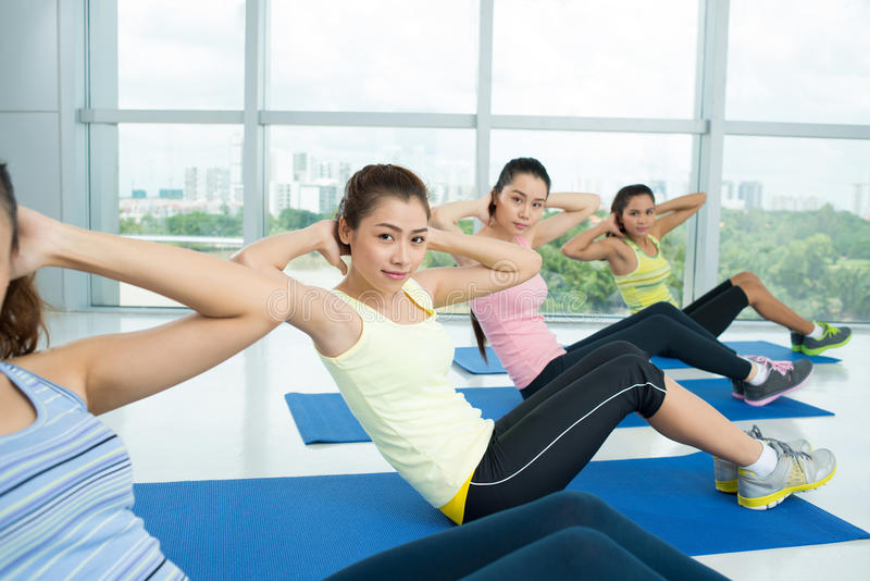 Sit-ups. Image of a young girl doing sit-ups in the aerobics class stock photography
