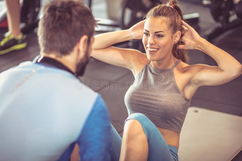 Sit-ups. Trainer assisting young women doing sit-ups at a gym. Focus is on man royalty free stock photos