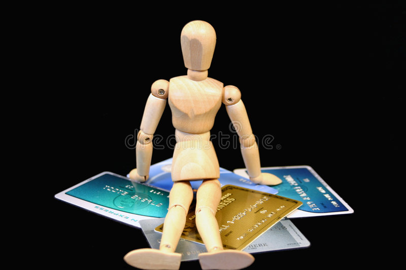 Sit on your money. Doll sitting on credit cards royalty free stock image